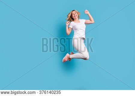 Full Body Photo Of Attractive Funny Crazy Lady Jump High Up Celebrating Holiday Raise Fists Astonish