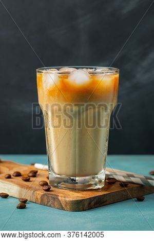 Ice Coffee In A Tall Glass With Cream Poured Over And Coffee Beans On A Light Stone Background. Cold