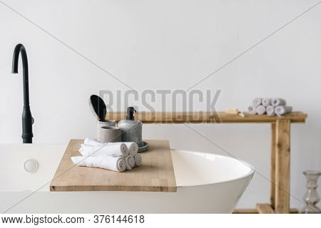 Hair Brush, Soap Dispenser And Clean Fresh Towels On Wooden Shelf Over White Contemporary Bath With