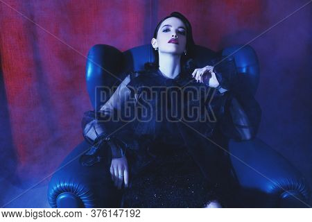 Portrait of a beautiful brunette young woman in fashionable black clothes sitting in a leather armchair in a luxury apartment. Beauty, fashion concept. Glamorous lifestyle.