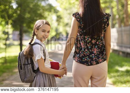 Happy Back To School. Back View Of Mother And Cute Daughter Holding Hand While Walking To School Alo