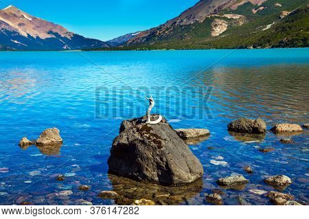 Huge lake with azure water and rocky beach by the lake. Pampas surround snow-capped mountains. Los Glaciares is Argentina's most beautiful natural park. Patagonia