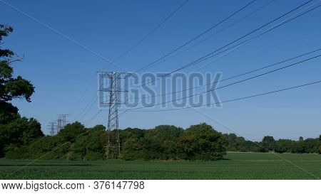 Pylon Against Deep Blue Sky Standing In Corn Field In Spring