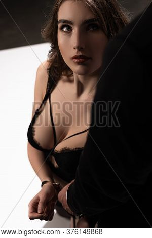 Dominant Man Touching Handcuffs On Submissive Woman In Black Bra