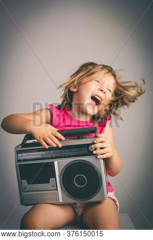 little girl has fun listening to music with an old 80's radio