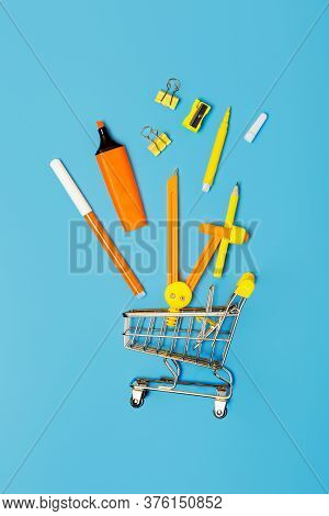 School Stationery And Mini Trolley On A Blue Background. Concept Back To School. Study Concept. Stat