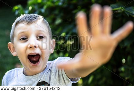 frightened child yelling and with open hand towards the camera.
