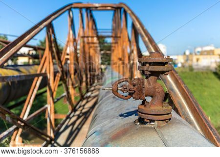 Old Rusty Iron Bridge Over The River With A Steam Pipeline. Heat Supply. Industrial Equipment. Detai