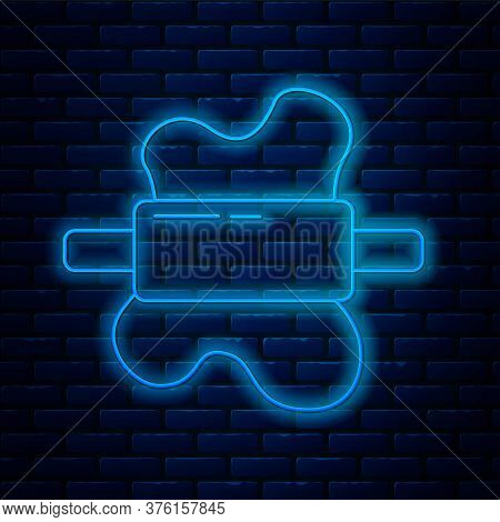 Glowing Neon Line Rolling Pin On Dough Icon Isolated On Brick Wall Background. Vector