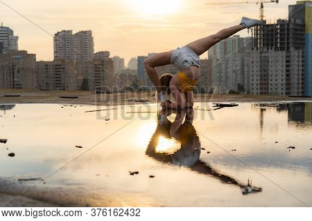Flexible Female Gymnast Doing Handstand And Calisthenic With Reflection In The Water On Cityscape Ba