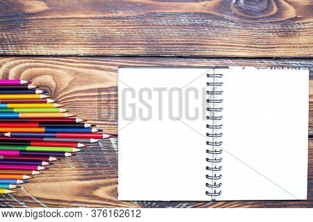 School Supplies Notebook And Color Pencils On A Wooden Table With, Top View