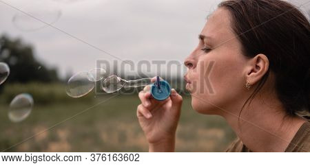 The Girl Blows Soap Bubbles. A Young Woman Sits In Nature And Blows Soap Balls. Face In Profile.