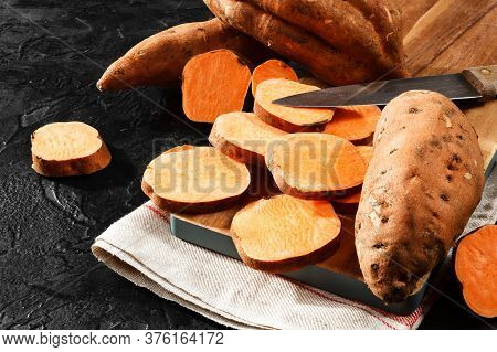 Organic Raw Sweet Potato Whole And Sliced On Wooden Kitchen Board.