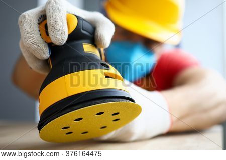 Close-up Of Male Worker Polishing Piece Of Wood With Modern Electrical Machine. Craftsman Wearing Fa