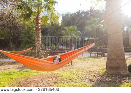 The Boy Lies In A Hammock. The Child Is Resting In Nature. Hammock Near A Wooden House.
