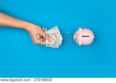 Female Hands Put Money In A Piggy Bank On A Blue Background. . Retirement Retention