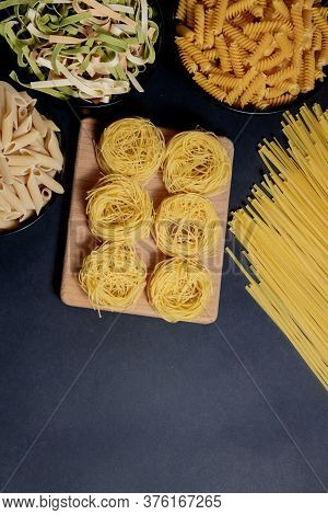 Different Types Of Dry Pasta On The Plate And In Bowls On Black Background. Space For Text, Top View