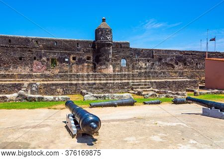 Bastion and loopholes in the thick ancient walls. Guns are on display in the fortress. Fort Jesus -  medieval fortification in Mombasa, Kenya. The concept of historical, educational and photo tourism