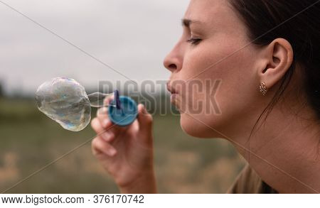 The Girl Blows Soap Bubbles. A Young Woman Sits In Nature And Blows Soap Balls. Face In Profile, Sid