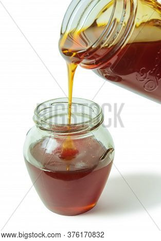 Dark Chestnut Honey Dripping From A Large Glass Jar In The Smaller Glass Jar, Isolated On A White Ba