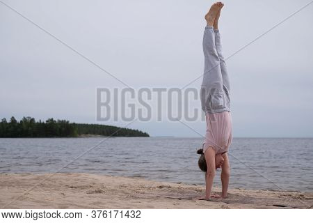 Woman Practicing Yoga Doing Handstand On Beach Outdoor.