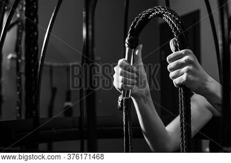 Female Hand With A Long Woven Leather Lash In A Cage. Bdsm Punishment And Pleasure. Cropped.