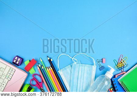 School Supplies And Coronavirus Prevention Items. Bottom Border On A Blue Paper Background. Back To