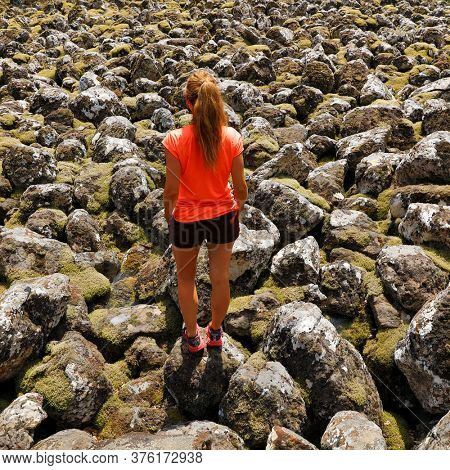 woman walking in old lava flow , calardez