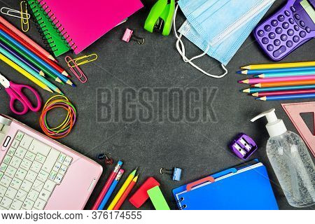 School Supplies And Covid 19 Prevention Items. Top View Frame On A Chalkboard Background. Back To Sc