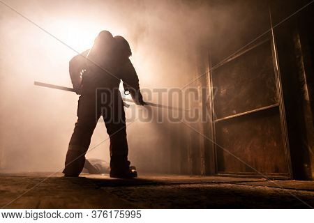 Silhouette of firefighter use metal hook to push away metal door for escape from burning building. Firefighter training  safety rescue from accident and public service concept.