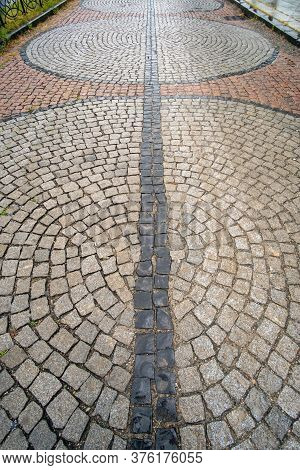 Traditional Wet Stone Pavement In Perspective After The Rain. Abstract Background Of Old Cobblestone