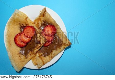 Fresh Thin Pancakes With Chocolate Paste And Strawberry On Blue Background With Copy Space. Russian,