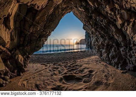 View From The Stone Cave On The Sunset, Sea And The Beach, The Volcanic Rock Of The Cave Is Lit By T