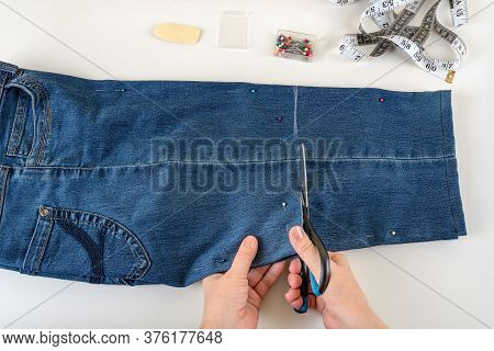 Caucasian Woman Hands Cutting Out A Folded In Half Blue Denim Capris With Scissors On A White Table.