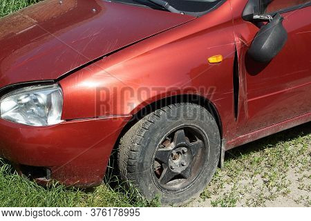 Part Of A Red Broken Passenger Car With A Broken Mirror And A Black Wheel On The Street