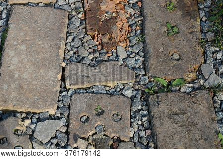 Stone Texture Of Pieces Of Brown Bricks And Gray Rubble In The Old Sidewalk On The Street