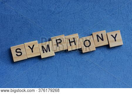 Text On Gray Word Symphony In Small Wooden Letters With Black Font On A Blue Background