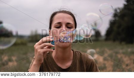 The Girl Blows Soap Bubbles. A Young Woman Sits In Nature And Blows Soap Balls. The Face In Front.