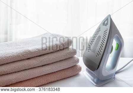 An Electric Iron And A Stack Of Ironed Towels On A Light Surface. Laundry Ironing, Economics, Househ
