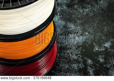 Three Coils Of Filament For 3d Printing. Bright Thermoplastic Of White, Orange And Red Colors. Reels
