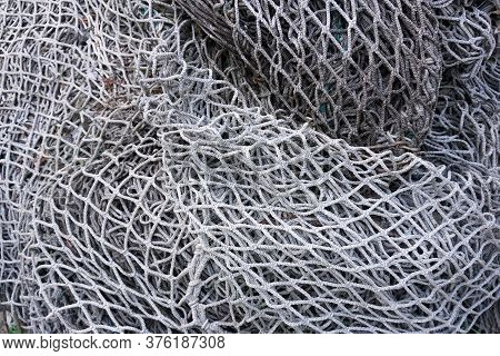Old Fishing Nets. A Closeup View Of An Old, Faded White Fishing Net Lying In A Pile. A Few Bits Of P