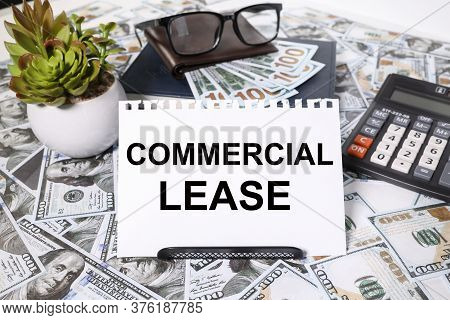 Text Commercial Lease. On A White Background. With Scrolled Money Bills On The Table, Calculator, Gl
