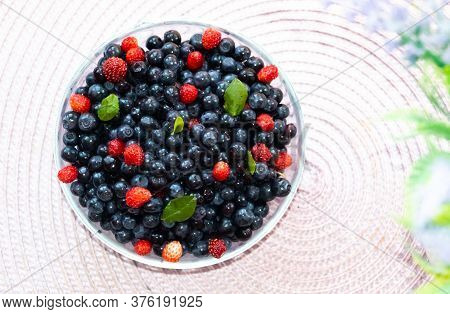 Fresh Bilberries And Strawberries Found In Forest. Bright Berries. Crop Of Bilberries And Wild Straw