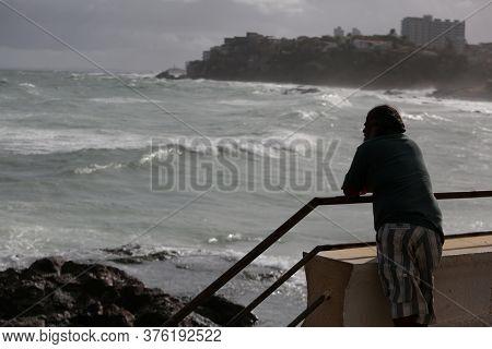 Salvador, Bahia / Brazil - July 4, 2017: Fisherman Observes The Rough Sea Near The Colony Of Fisherm