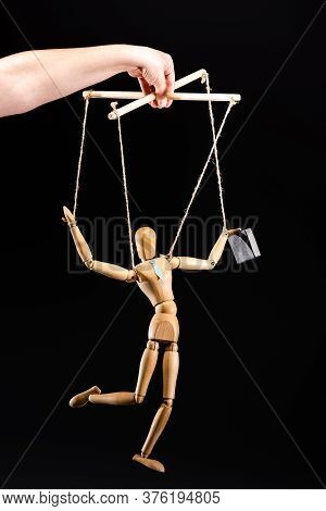 Cropped View Of Puppeteer Holding Wooden Marionette In Tie Isolated On Black