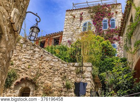 Stone Exterior Of Old Buildings With Flowers On The Streets Of Eze Village, Picturesque Medieval Cit