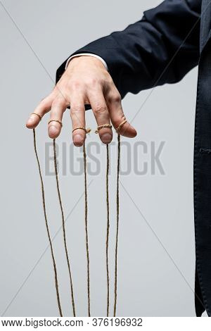Partial View Of Puppeteer In Suit With Strings On Fingers Isolated On Grey