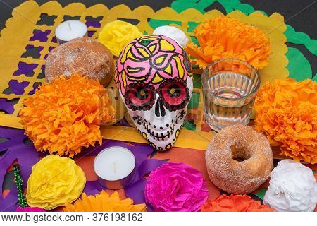 Part Of A Mexican Day Of The Dead Offering Altar With A Hand Painted Skull, Flowers, Candles, Mezcal