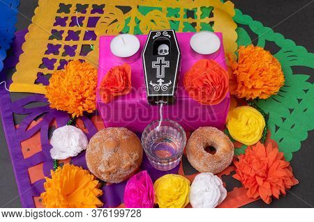 Mexican Day Of The Dead Altar With Traditional Bread, Colorful Flowers, A Coffin, Mezcal, Candles An