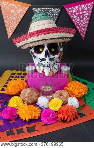 Mexican Day Of The Dead Altar With Traditional Bread, Colorful Flowers, Banner, A Hand Painted Skull